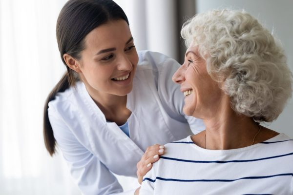 stock-photo-caring-smiling-young-nurse-taking-care-supporting-happy-elder-grandma-patient-female-doctor-1562123101